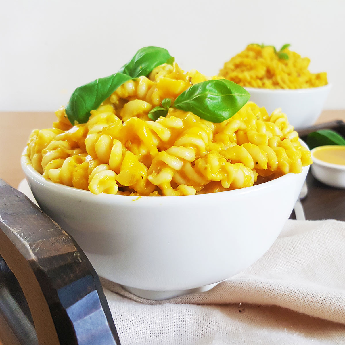 Vegan Pumpkin pasta served in a white bowl, garnished with basil leaves