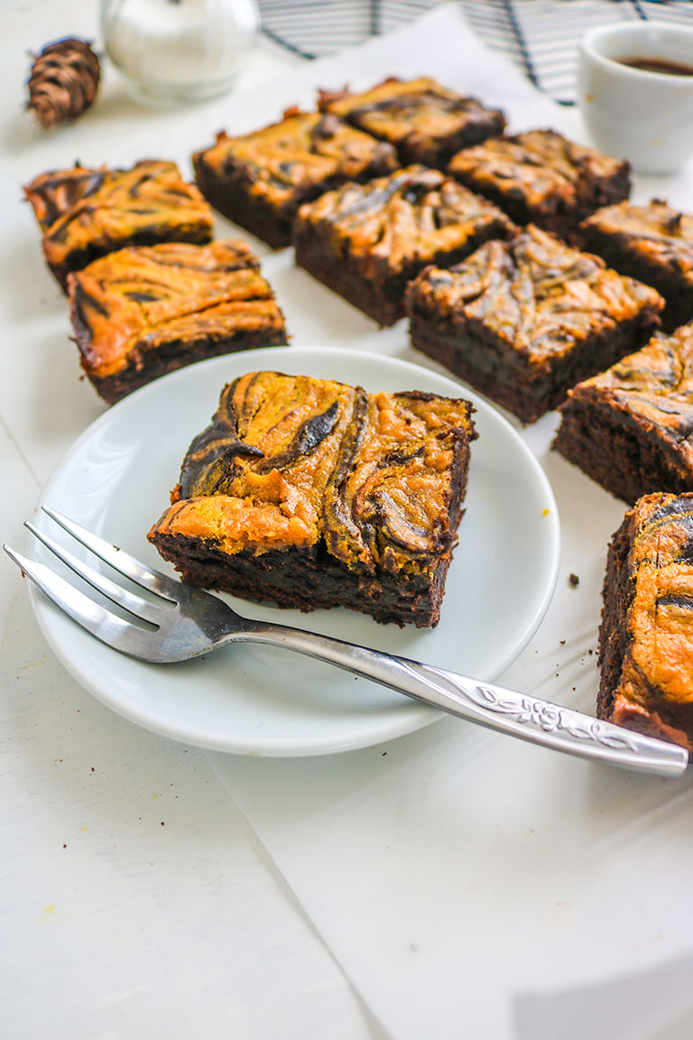 vegan pumpkin brownies on a white plate and silver fork