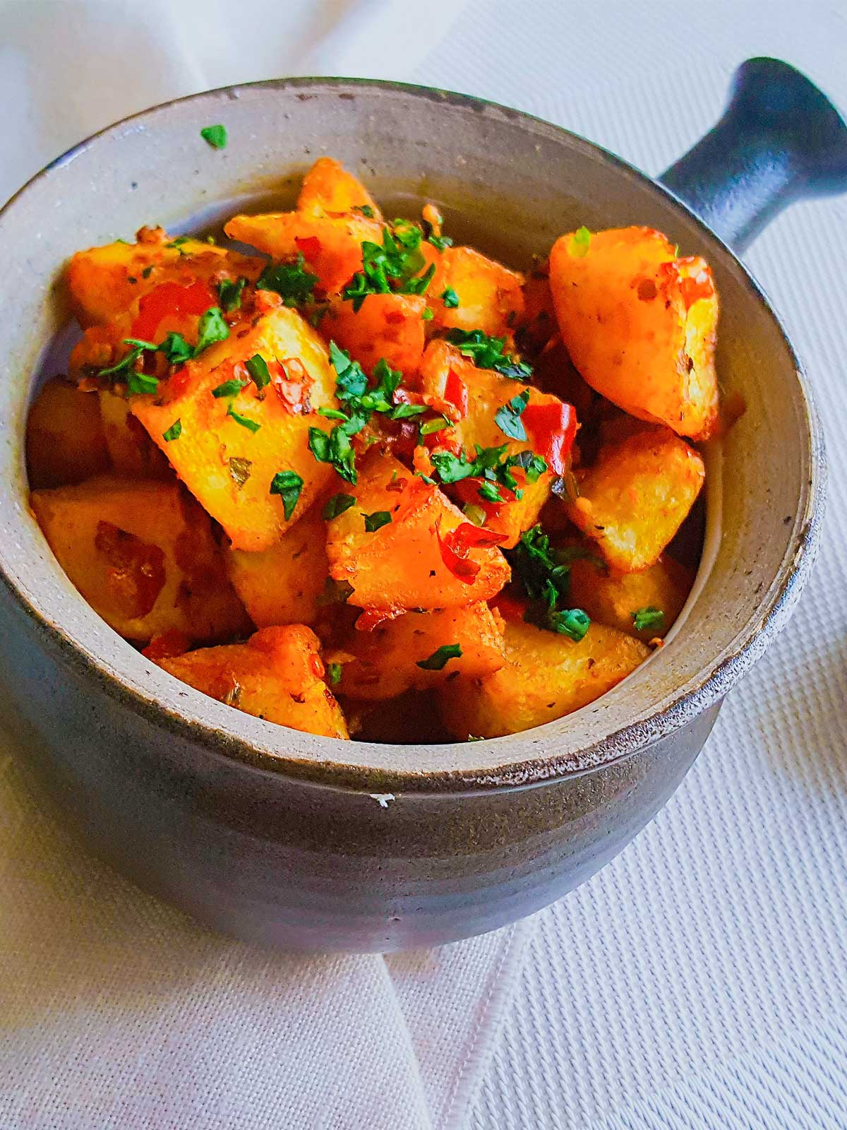 Batata Harrah served in a Bowl topped with cilantro and chilies