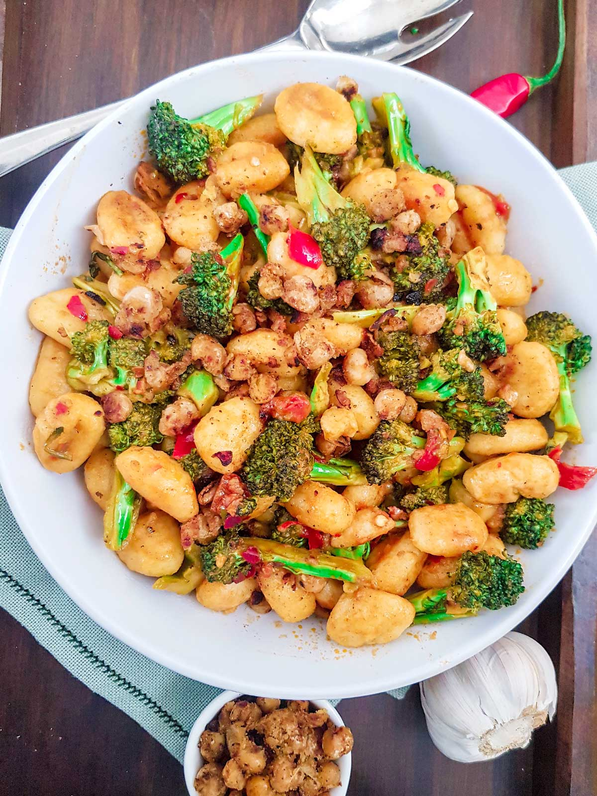 Pan fried gnocchi with broccoli served in a white bowl topped with chickpea crumble