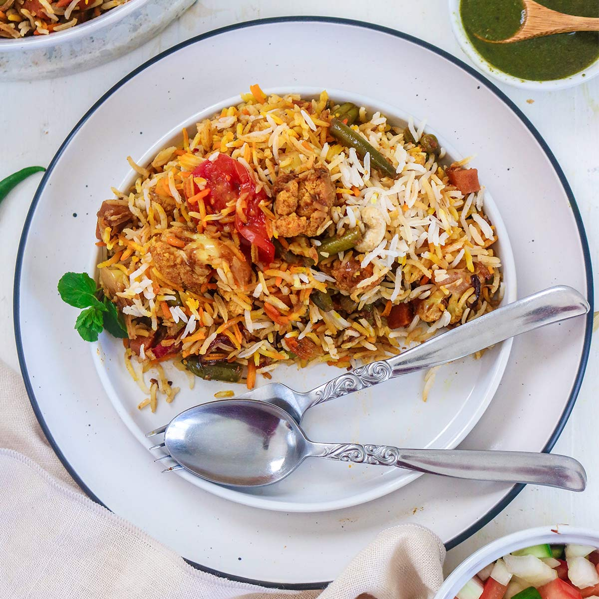 vegan biryani served in a plate with fork and spoon
