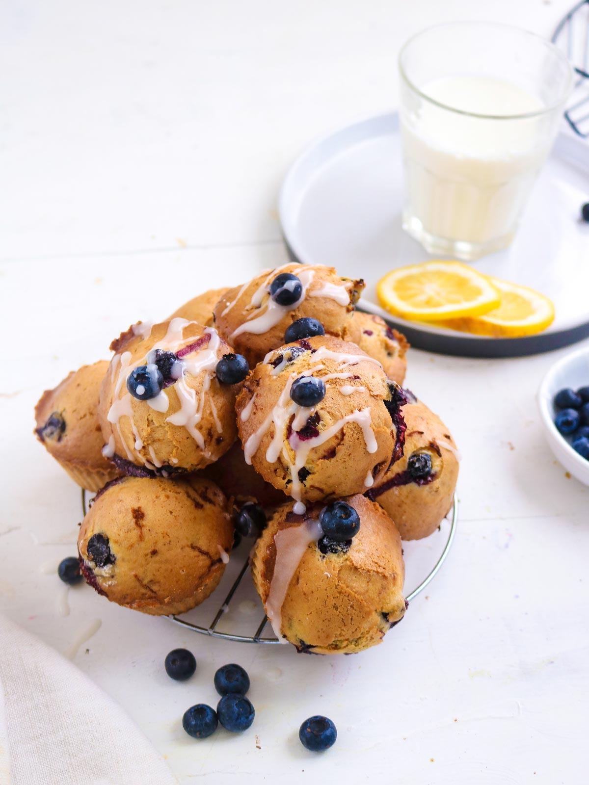 Vegan Blueberry lemon muffins topped with sugar lemon glaze. stack on a wire rack .