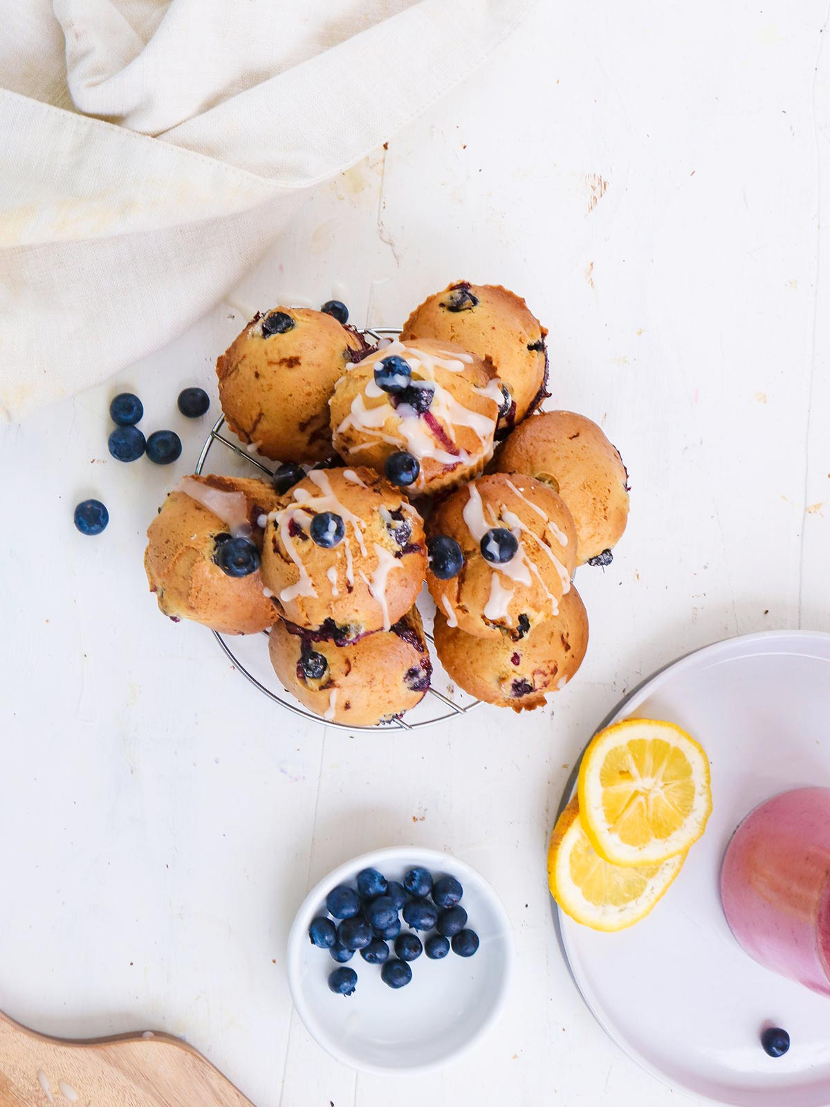 Vegan Blueberry lemon muffins topped with sugar lemon glaze. stack on a wire rack top view