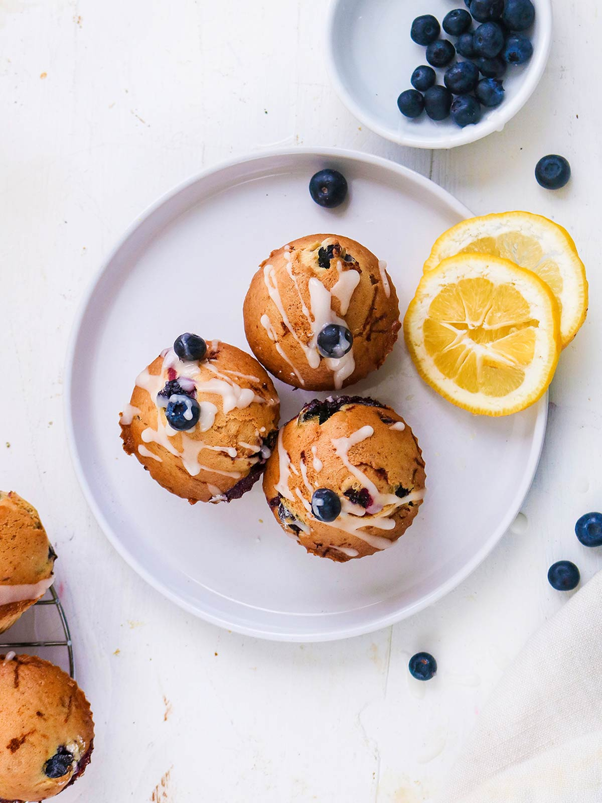 Vegan Blueberry lemon muffins served on top with lemon slices on side.