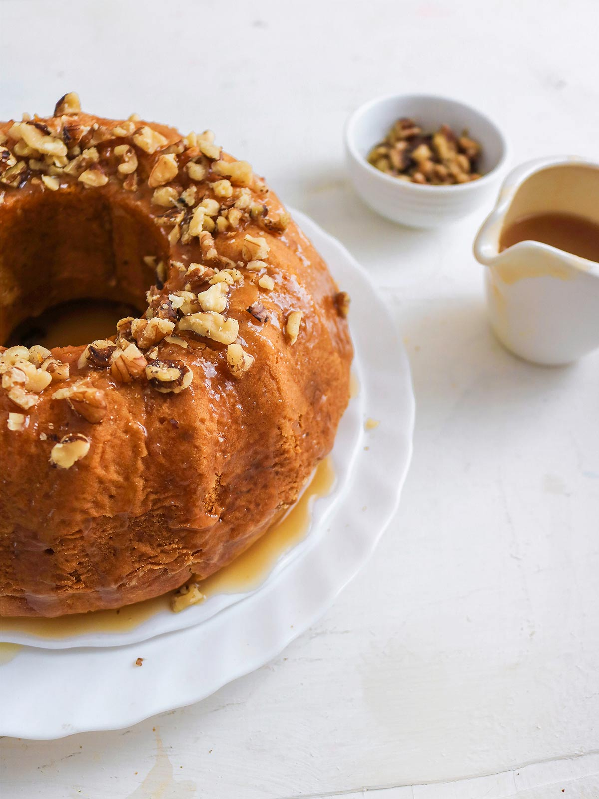 Vegan pumpkin bundt cake topped with caramel glaze and chopped walnuts