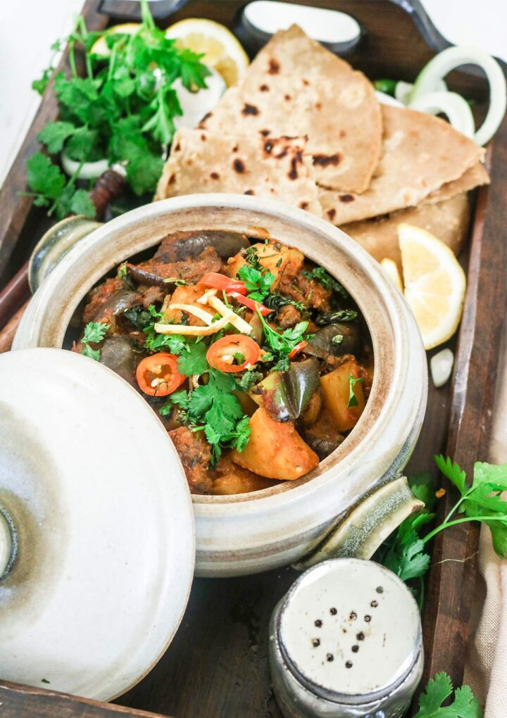 eggplant curry in a pot served over wooden tray