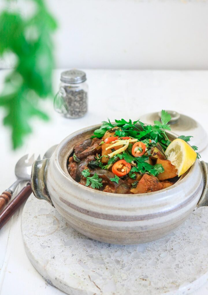 Aloo baingan served in a ceramic pot , garnished with chilies and parsley.