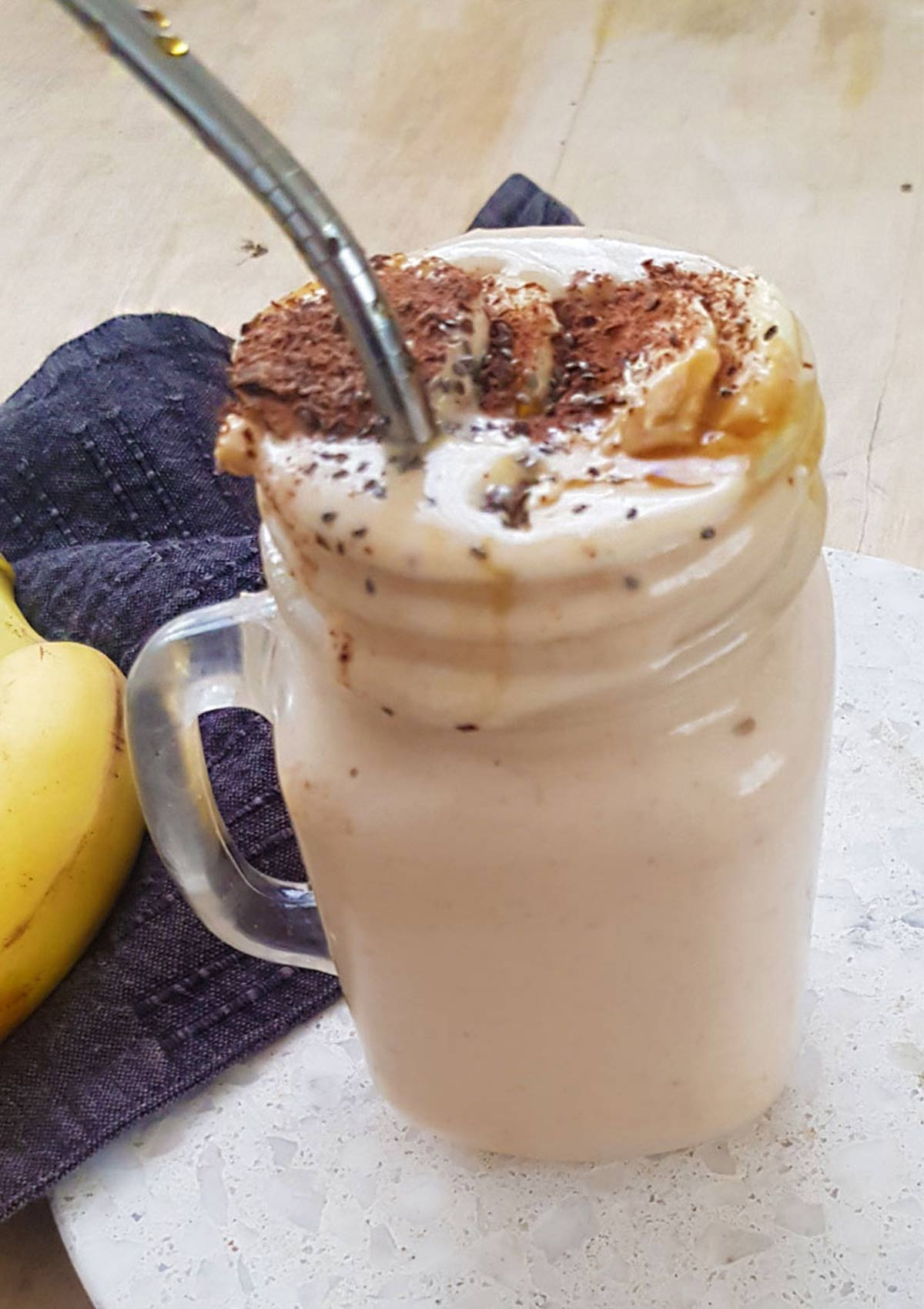 peanut butter banana smoothie in a glass jar with metal straw