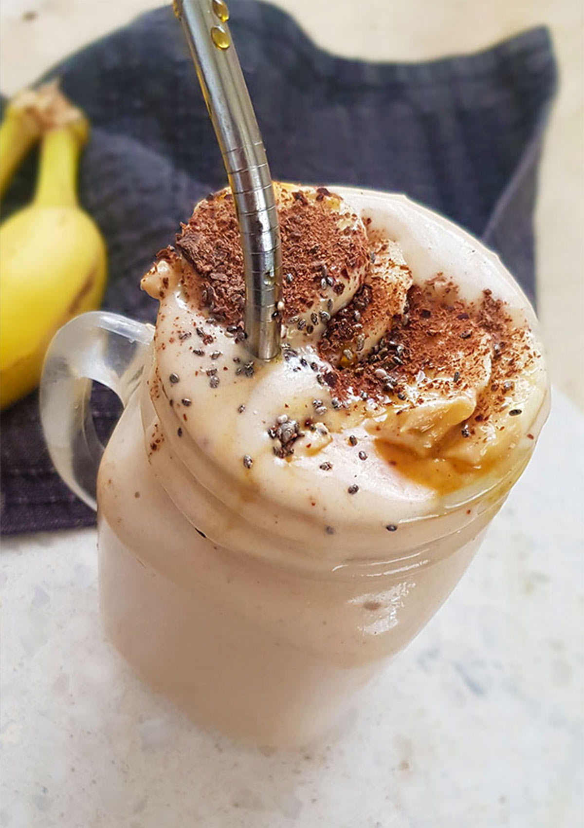 Banana peanut butter smoothie topped with banana slices and chia seeds.