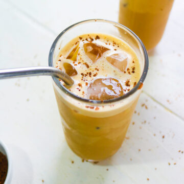 Iced oat milk latte in a glass with metal straw