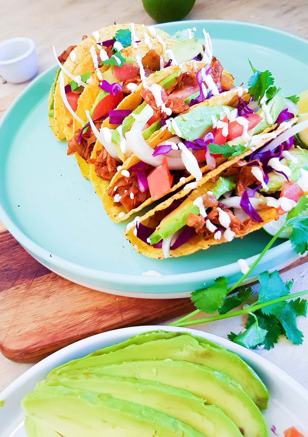 Hard shell tacos filled with jackfruit, avocado,and cabbage.