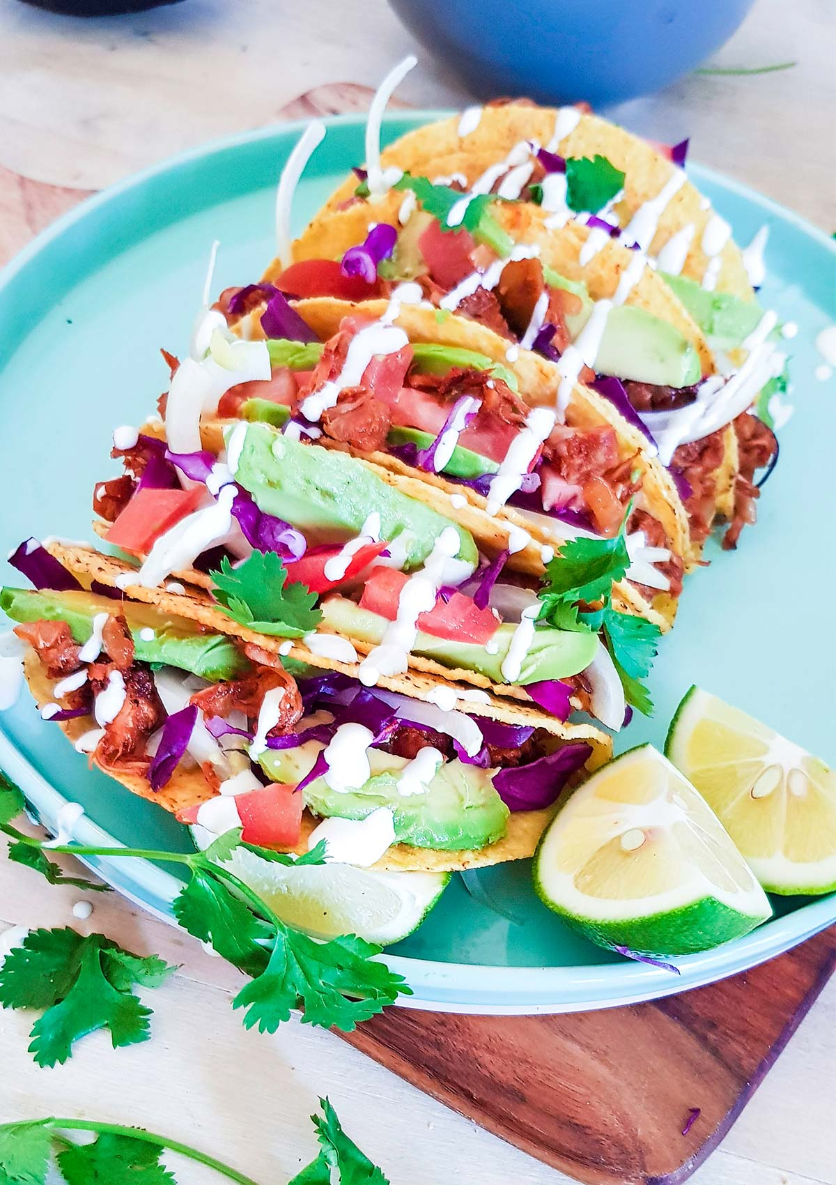 side view of tacos placed in plate with a slice of lime