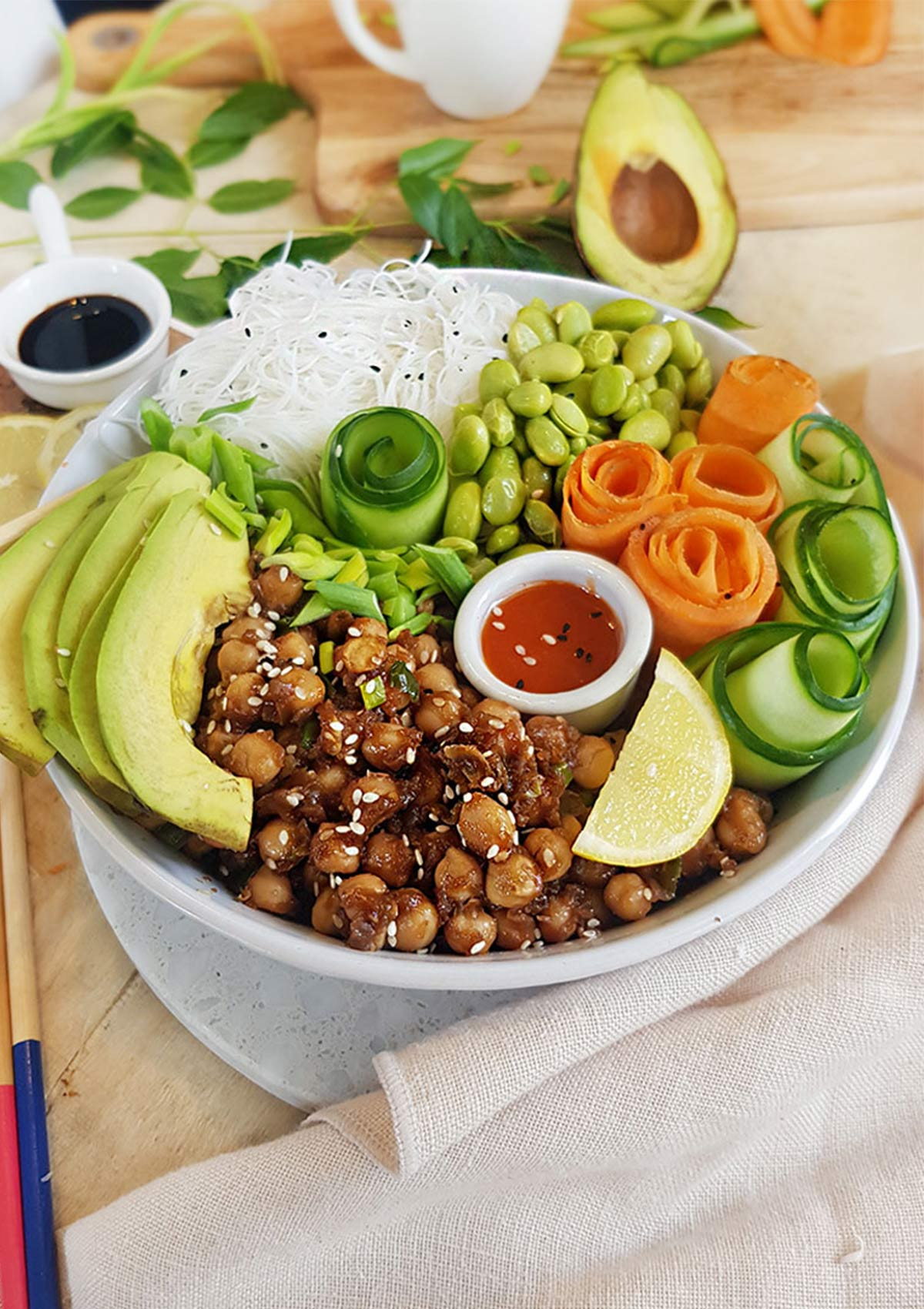 poke bowl of chickpeas with carrot and cucumber rolls , edamame , avocado and rice noodles.
